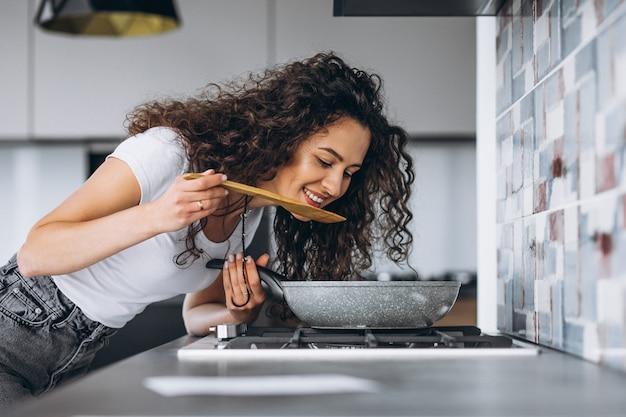 Frauenkocher, der nudeln an der küche macht