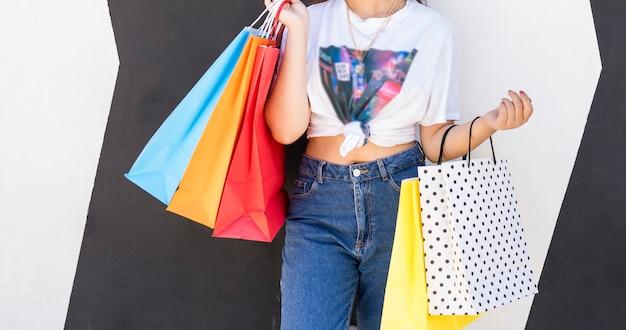 Frauenkörper hält mit ihren händen bunte einkaufstaschen im einkaufszentrum