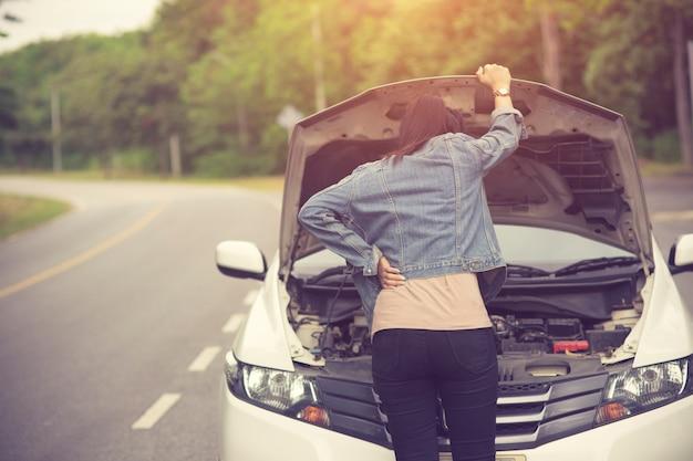 Frauenkontrolle sie öffnete die motorhaube kaputtes auto an der seite sehen sie beschädigte oder beschädigte motoren