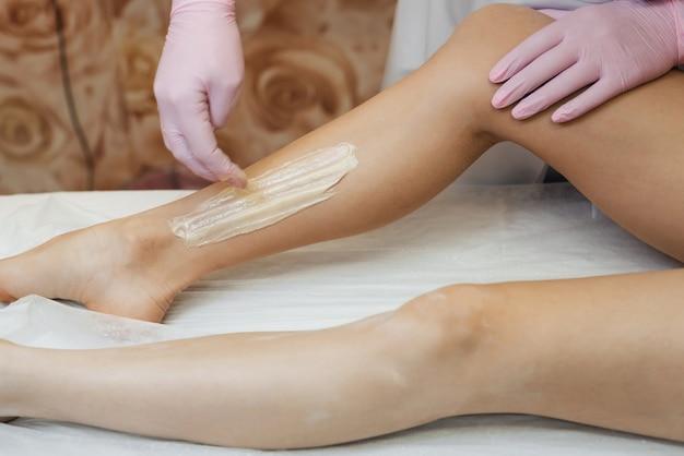 Frauenkosmetiker im verfahren des entfernens des haares auf den beinen eines mädchens mit zuckerdepilation