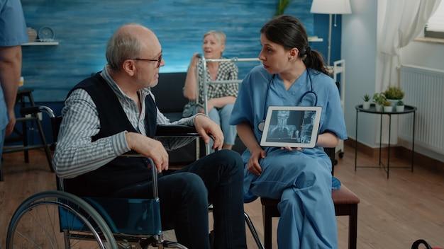 Frauenkrankenschwester mit röntgenstrahl auf tablette, der dem alten patienten einen scan zeigt