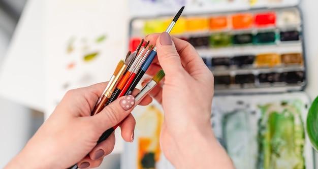 Frauenkünstlerhände halten pinsel und wählen einen zum zeichnen mit aquarell with