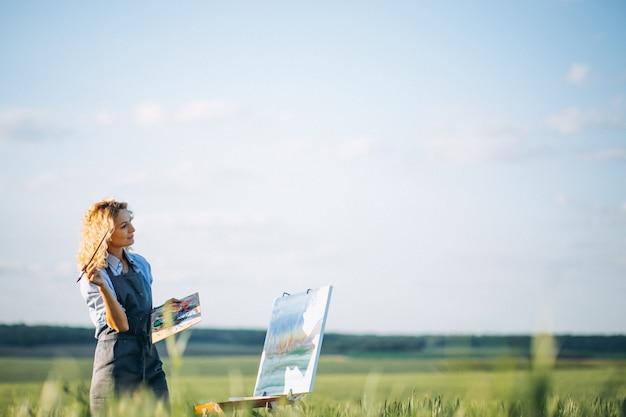 Frauenkünstlermalerei mit ölfarben auf einem gebiet