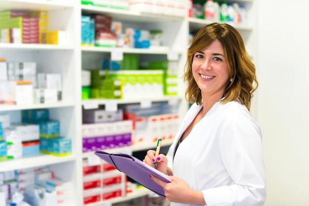 Frauenkunde mit einem ordner in der apotheke