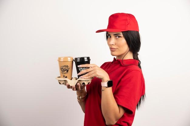 Frauenkurier, der kaffeetassen auf weißem hintergrund hält. hochwertiges foto