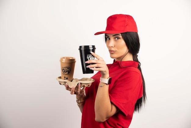 Frauenkurier, der kaffeetassen auf weißem hintergrund zeigt. hochwertiges foto