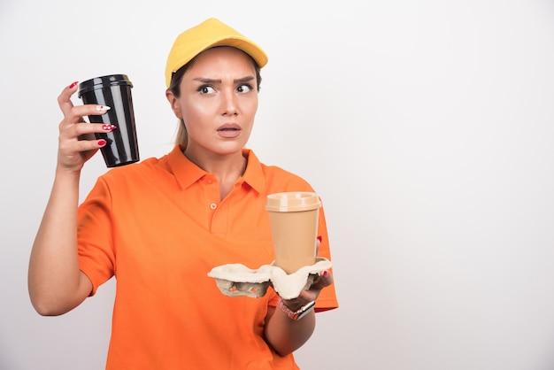 Frauenkurier, der zwei tassen kaffee auf weißer wand hält.