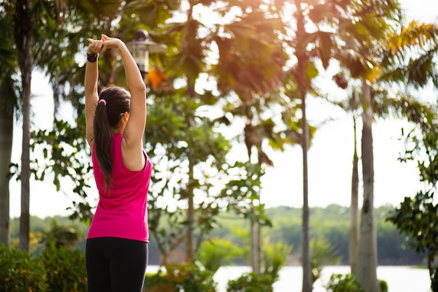 Frauenläufer, der arm ausdehnt, bevor sie in den park laufen. outdoor-trainingskonzept.