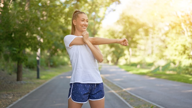 Frauenläufer, der arme streckt, bevor er sommerparkmorgen ausübt