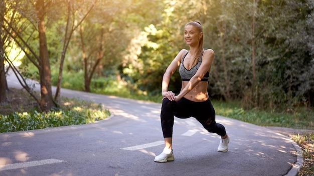 Frauenläufer, der beine streckt, bevor sommerparkmorgen ausgeübt wird