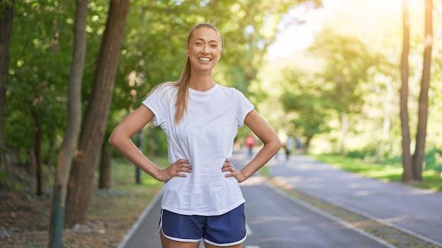 Frauenläufer, der vor dem ausüben des sommerparkmorgens steht