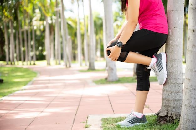 Frauenläufer-gefühlsschmerz auf ihrem knie im park. übungsaktivitäten.