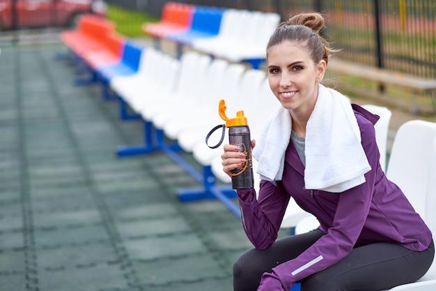 Frauenläufer mit stillstehendem und trinkwasser des tuches von einer flasche, nachdem bahnlauf des stadions ausgearbeitet worden ist