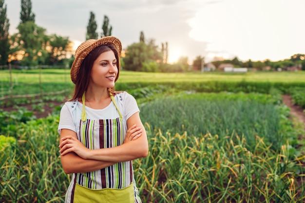 Frauenlandwirt, der gemüse auf gemüsegarten in der landschaft betrachtet. landwirtschaft und landwirtschaftskonzept