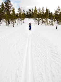 Frauenlanglauf in der schneebedeckten landschaft des winters