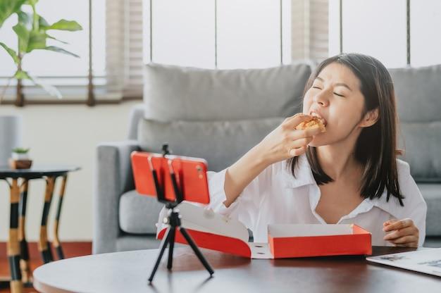 Frauenlebensmittelblogger, der pizza beim herstellen des neuen zufriedenen videos isst