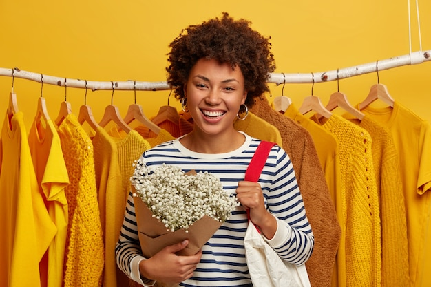 Frauenlebensstil, mode, konsumkonzept. afroamerikanerin mit fröhlichem gesichtsausdruck, steht im bekleidungsgeschäft, trägt einkaufstasche auf der schulter, bekommt blumen vom ehemann, gelber hintergrund