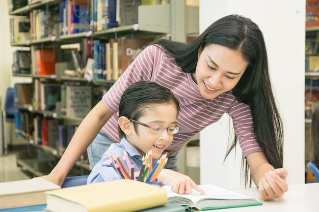 Frauenlehrer und kinderstudent lernen mit buch am bücherregalhintergrund