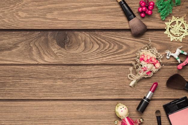 Frauenmake-upbürsten, lippenstift und weihnachtsverzierungen auf holz