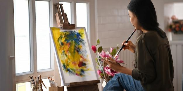 Frauenmalerei auf leinwand mit pinsel beim sitzen am stuhl