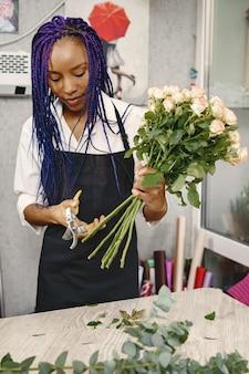 Frauenmanager, der am arbeitsplatz steht. dame mit pflanze in händen. famale schneidet blumen. floristenkonzept.