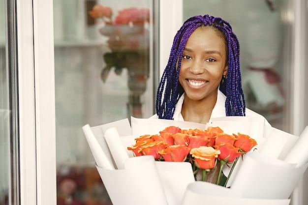 Frauenmanager, der am arbeitsplatz steht. dame mit pflanze in händen. glücklicher weiblicher florist im blumenmittel-floristenkonzept.