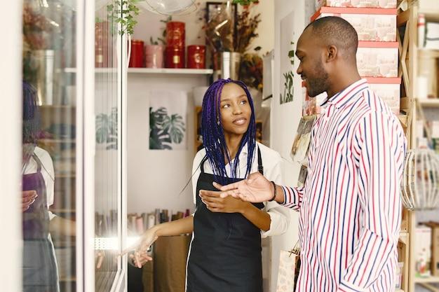 Frauenmanager, der am arbeitsplatz steht. dame mit pflanze in händen. mann, der blumen kauft.