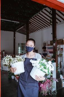 Frauenmanager, der gesichtsmaskenflorist trägt, der einen eimer blumen hält