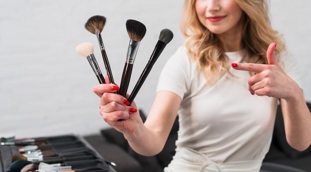 Frauenmaskenbildner, der auf make-upbürsten zeigt