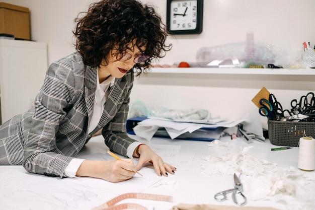 Frauenmode-hochzeitsdesigner, der brautkleider mit einem bleistift skizziert, der eine neue sammlung schafft