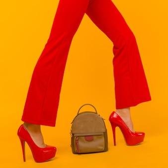 Frauenmode mit schöner kleiner rucksackhandtasche mit roten schuhen der hohen absätze auf gelbem hintergrund