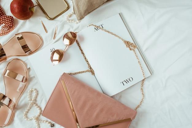 Frauenmode rosa gestyltes konzept. bijouterie, accessoires auf weißem leinen. hausschuhe, handtasche, leeres magazinblatt