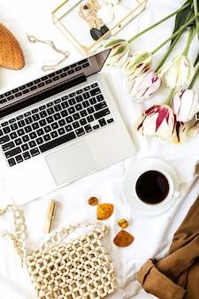 Frauenmode schönheit blog home office schreibtisch arbeitsbereich. laptop, tulpenblumenstrauß, kleidung und accessoires