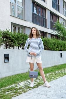Frauenmodel posiert in neuer kleiderkollektion im park in der nähe des hauses