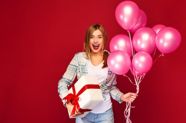 Frauenmodell, das schachtel mit geschenkgeschenk und rosa luftballons feiert und hält