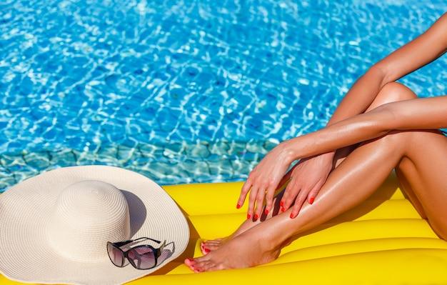 Frauenmodell entspannt sich im schwimmbad. beine mit hut schließen