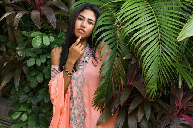 Frauenmodell im boho-kleid mit grünen palmblättern. schöne asiatische frau in den modischen sommerkleidern und -zubehör, die im tropischen naturporträt aufwerfen.