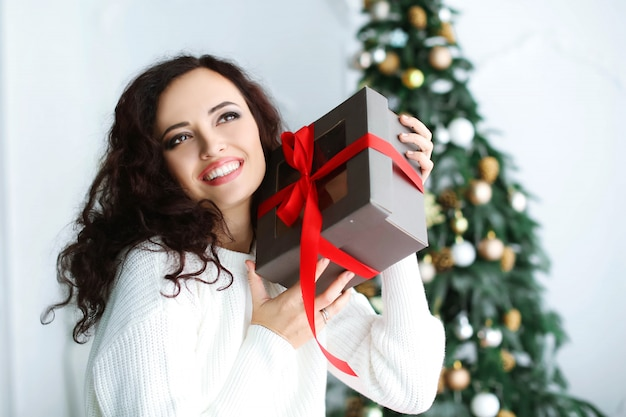 Frauenmodell in einem roten kleid in einem fotostudio, das ein neujahrsgeschenk in ihren händen hält.