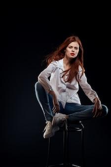 Frauenmodell in jeans und in einem weißen hemd, das auf einer schwarzen wand aufwirft