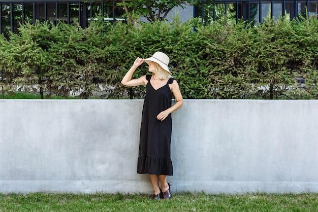 Frauenmodell in schwarzem kleid und hut posiert in neuer kleiderkollektion