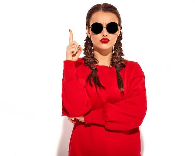 Frauenmodell mit hellem make-up und den bunten lippen mit zwei zöpfen und sonnenbrille in der roten kleidung des sommers lokalisiert. hat eine gute vorstellung davon, wie man ein projekt verbessern kann, hebt den finger