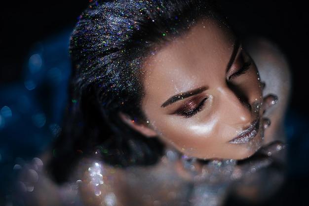 Frauenmodell mit make-up und funkeln auf einem nackten körper