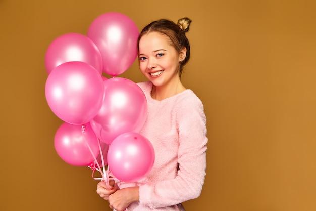 Frauenmodell mit rosa luftballons auf goldener wand