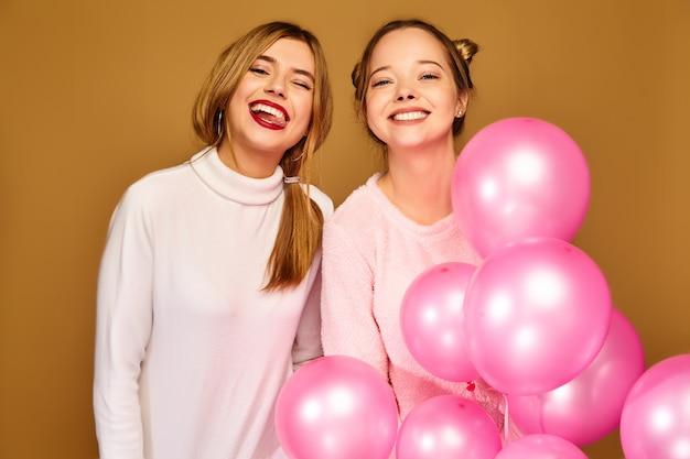 Frauenmodelle mit rosa luftballons auf goldener wand