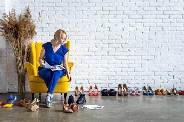 Frauenmodestylistin, die mit papiermagazinskizze arbeitet, die outfit zusammenstellt, das schuhe wählt