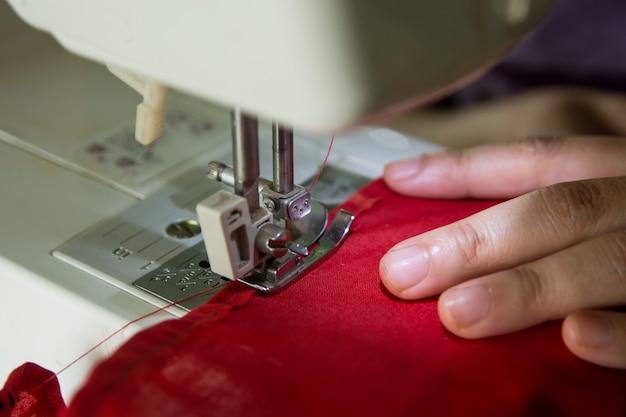 Frauennäherin, die kleidung auf einer nähmaschine machend arbeitet.