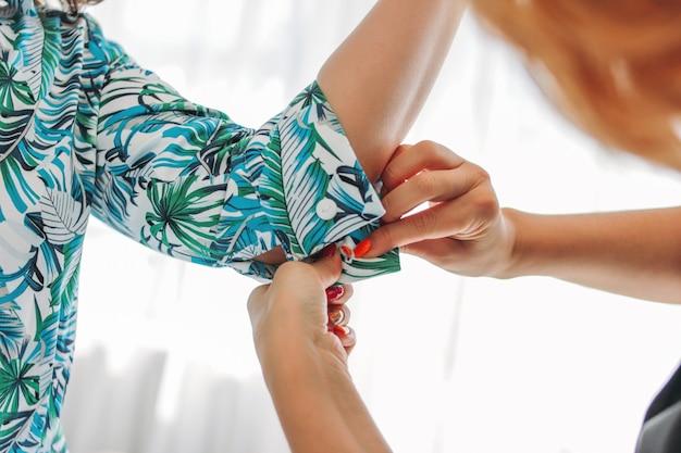 Frauennäherin, stylist oder verkaufsberater knöpft auf dem ärmel des kunden