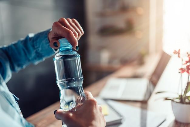 Frauenöffnungsflasche wasser im büro