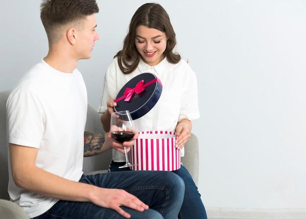 Frauenöffnungsgeschenkbox auf couch