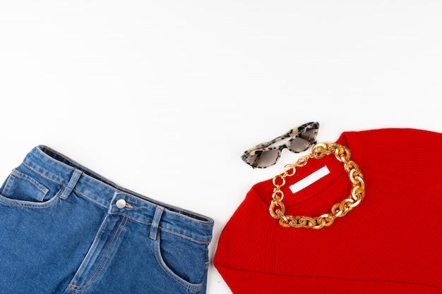 Frauenoutfit mit rotem pullover und accessoires auf weiß
